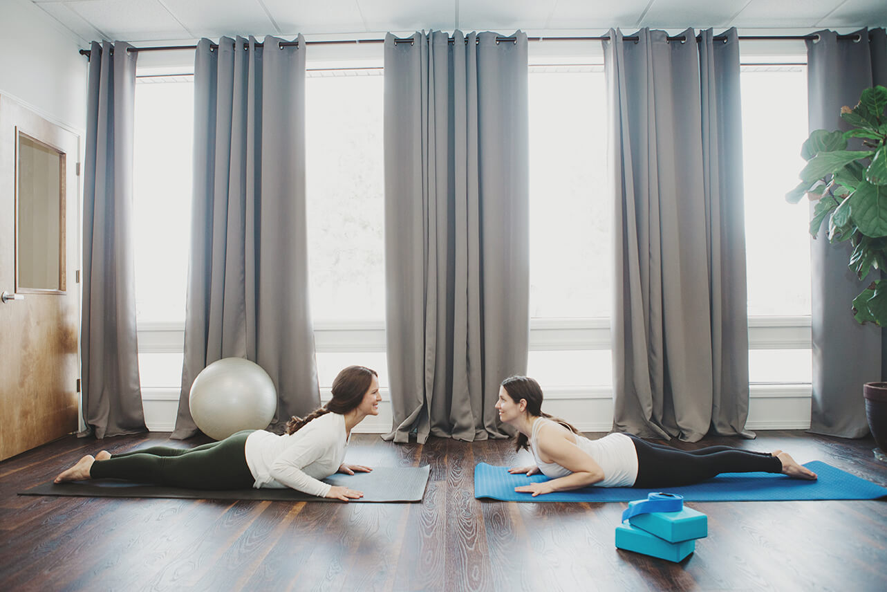 two people on the floor facing each other doing yoga