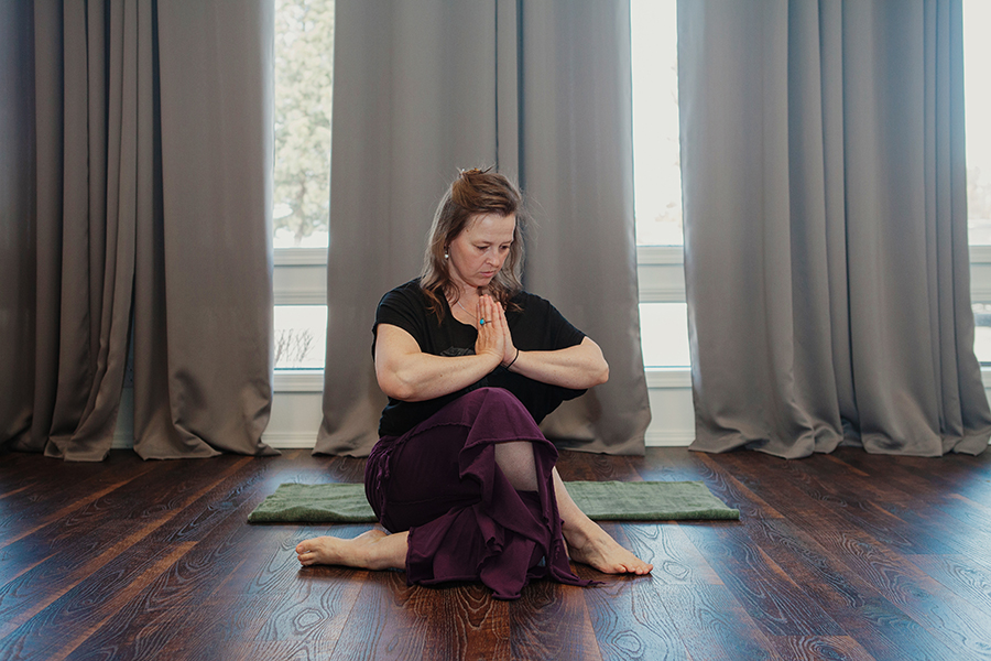 woman sitting on the floor with her knees crossed and her hands in a prayer position